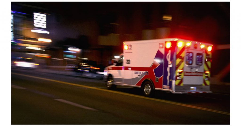 Photo of an ambulance speeding through traffic at nighttime