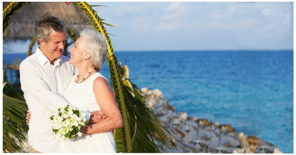 Photo of a senior couple gazing into each other's eyes while getting married on the beach
