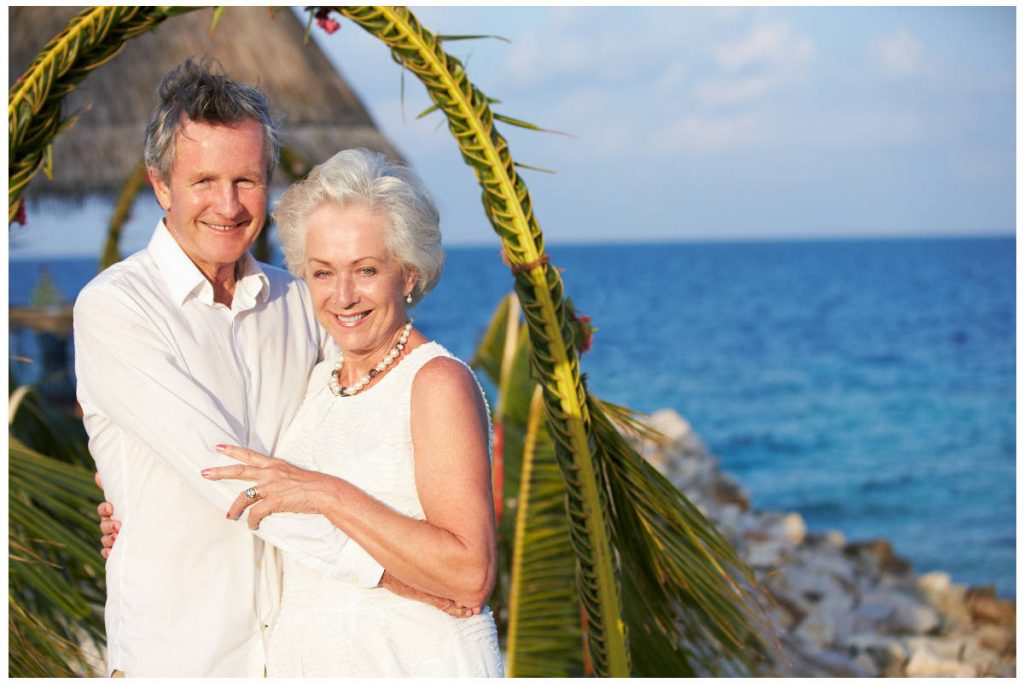 Photo of senior couple smiling in their Beach wedding with the ocean in the background.